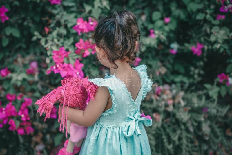 Liten brunettflicka i en mintkaramellfärgklänning i trädgården Gullig barninnehavdocka arkivfoto