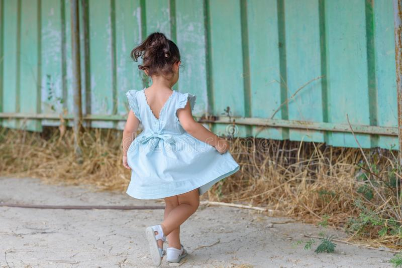 Liten brunettflicka i en utomhus- mintkaramellfärgklänning royaltyfria foton