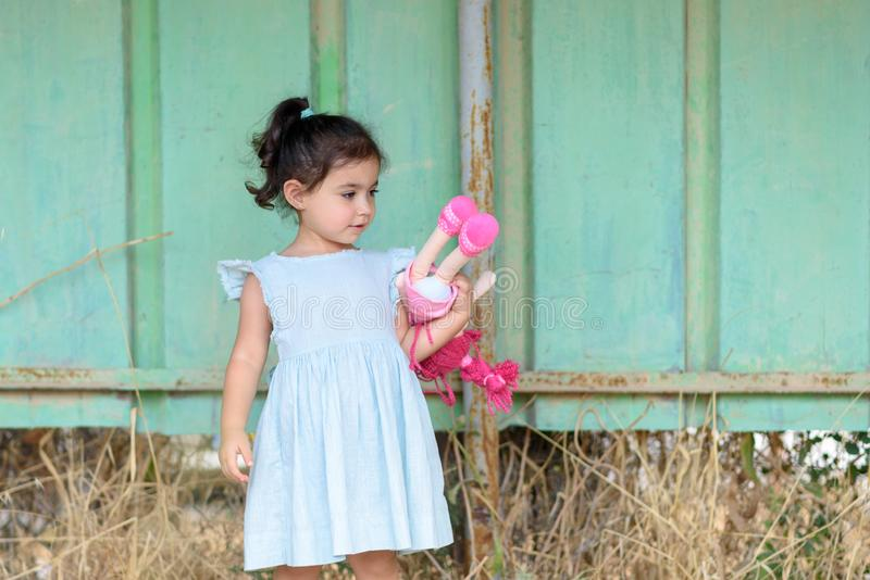 Liten brunettflicka i en utomhus- mintkaramellfärgklänning Gullig barninnehavdocka arkivfoton