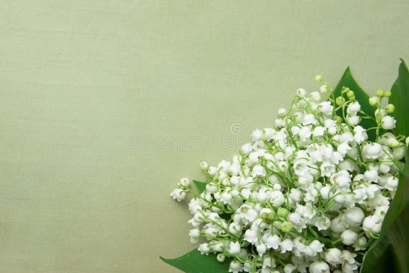 Liten bukett av liljekonvaljblommor med gröna sidor på beige tappningbakgrund Dag för ` s för kvinnor för ` s för bröllopfödelsed royaltyfria foton