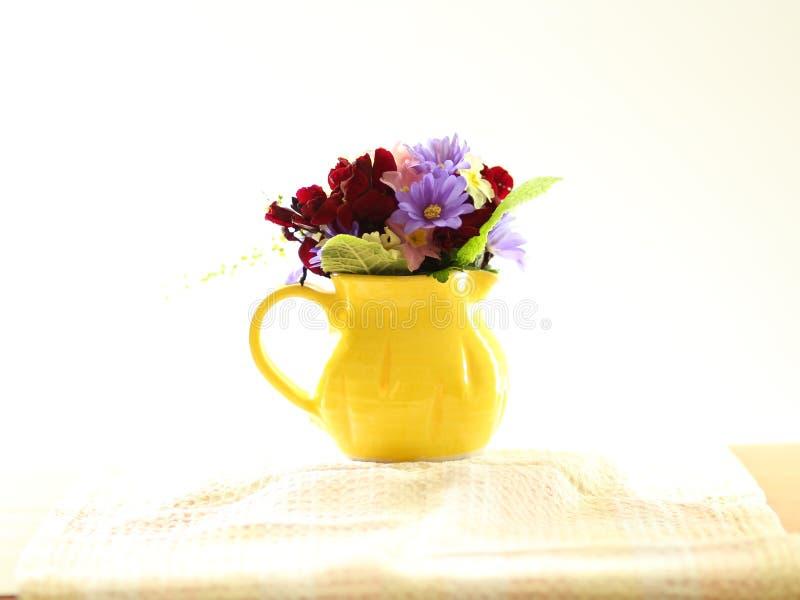 Liten liten bukett av vårblommor i en liten gul tillbringare royaltyfri bild