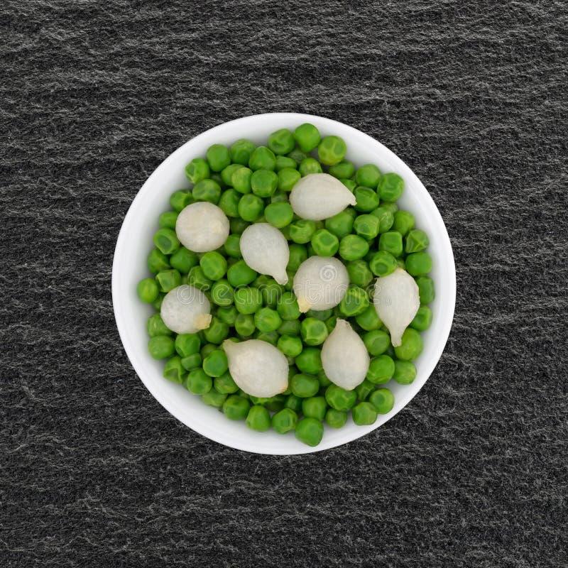 Liten bunke med lagade mat pärlemorfärg lökar och gröna ärtor royaltyfri fotografi