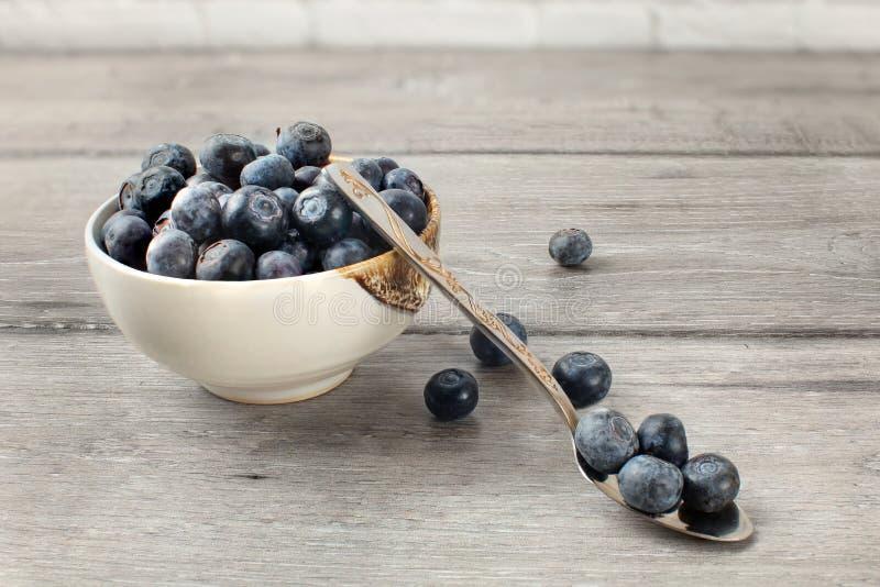 Liten bunke mycket av blåbär, med skeden och någon spilld berr royaltyfria bilder