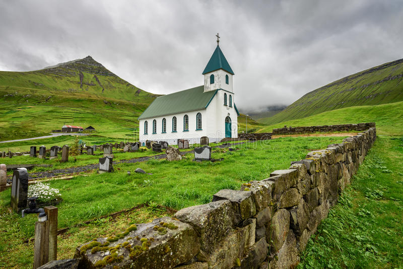 Liten bykyrka med kyrkogården i Gjogv, Faroe Island, Danmark royaltyfri foto