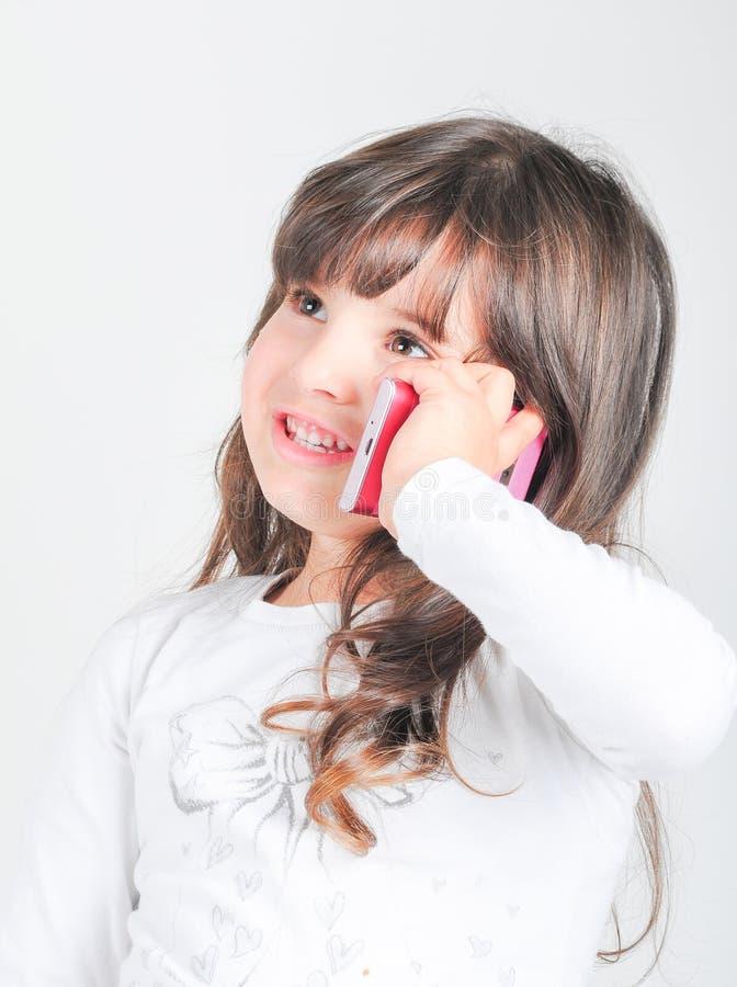 Liten caucasian flicka med mobiltelefonen royaltyfri bild