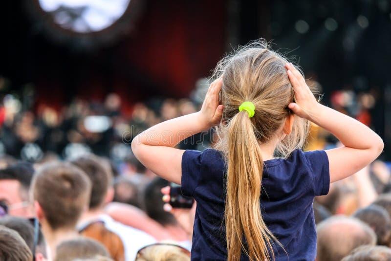 Liten Caucasian flicka på faders skuldror som håller ögonen på konserten i folkmassan arkivbild