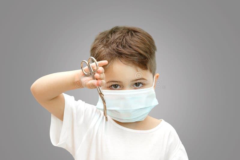 Liten Caucasian pojke i en medicinsk maskering p? en isolerad bakgrund som rymmer medicinsk sax royaltyfri fotografi