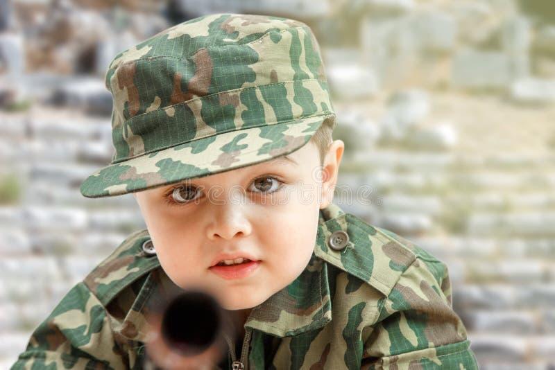Liten Caucasian pojke i milit?r kl?der och med leksakvapen p? bakgrunden av den f?rst?rda byggnaden royaltyfria bilder