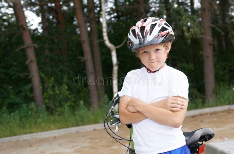 Liten Caucasian pojke i skyddande hjälmställningar som lutar på cykeln som poserar för kameran Tonåring som är klar att rida royaltyfria foton