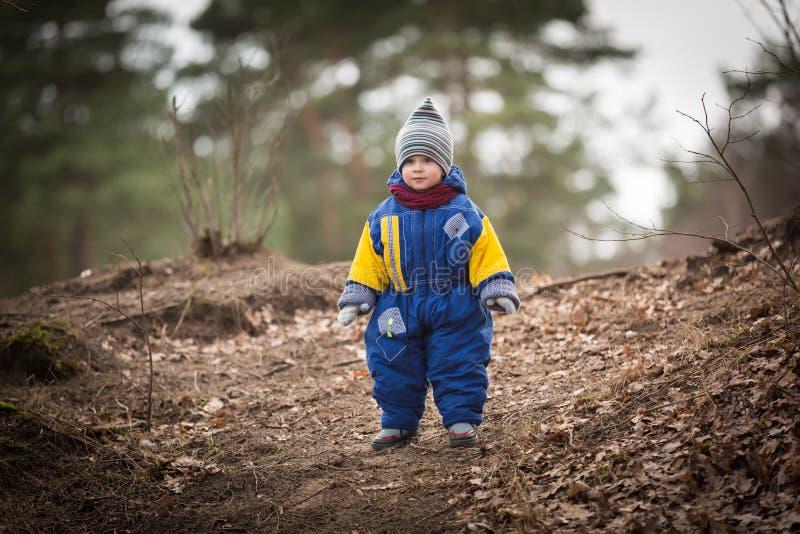Liten caucasian pojke som spelar i skog på den tidiga våren royaltyfria bilder