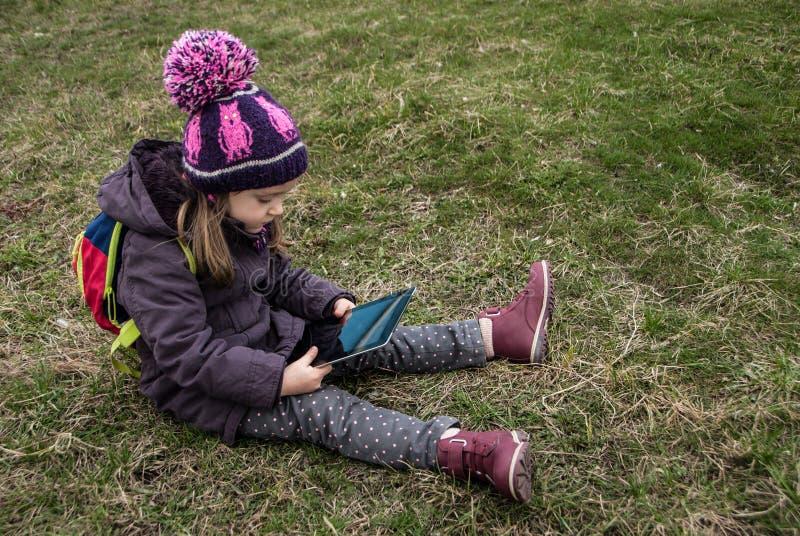 Liten childgirl som sitter på ett gräs och en hållande ögonen på digital apparat royaltyfri fotografi