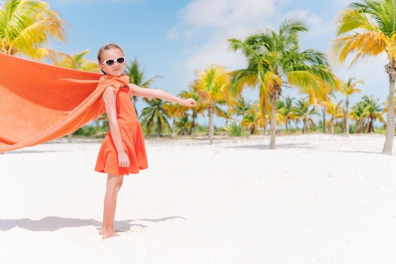 Liten cutieflicka som spelar superheroen p? en tropisk strand royaltyfri bild