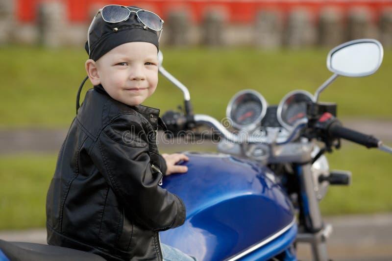 Liten cyklist på vägen med motorcykeln arkivbild