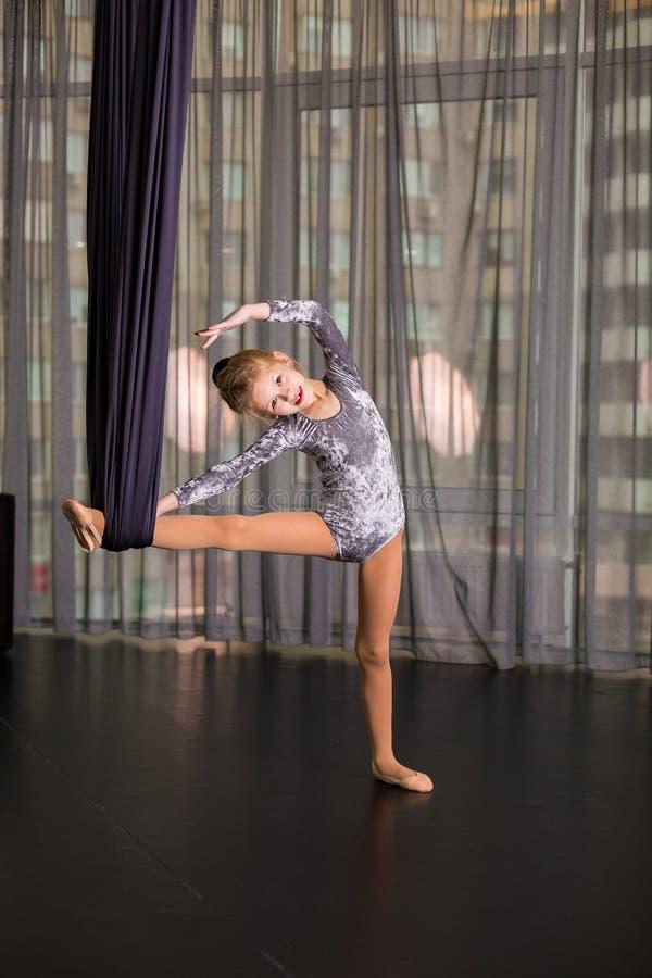 Liten dansare i en flyg- yogahängmatta arkivfoto