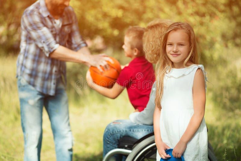 Liten daugher av en rörelsehindrad kvinna ler på kameran royaltyfria foton
