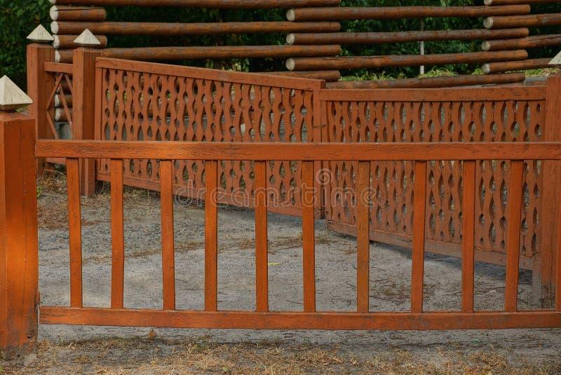 Liten dekorativ brun grind tillverkad av skivor på en grå sidopromenad royaltyfri fotografi