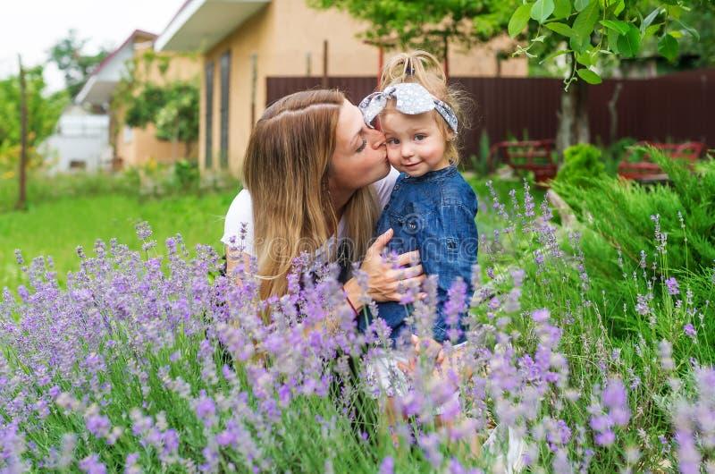 Liten dotter för ung caucasian moderkyss utomhus Familjen vilar i byn arkivbild