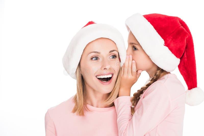Liten dotter i den santa hatten som viskar i öra av att le modern, royaltyfri bild