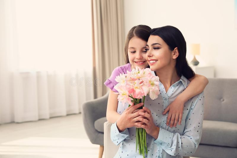 Liten dotter som hemma gratulerar hennes mamma, utrymme för text royaltyfria bilder