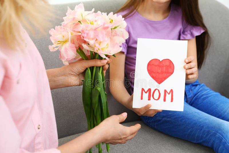 Liten dotter som hemma gratulerar hennes mogna mamma lycklig moder s för dag arkivfoto