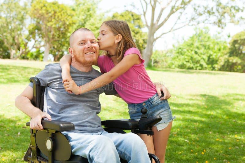 Liten dotter som kysser henne rörelsehindrad fader arkivfoton