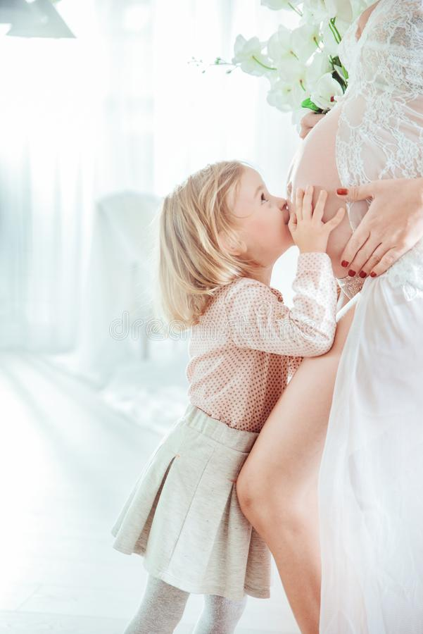 Liten dotter som kysser hennes buk för moder` s royaltyfria bilder