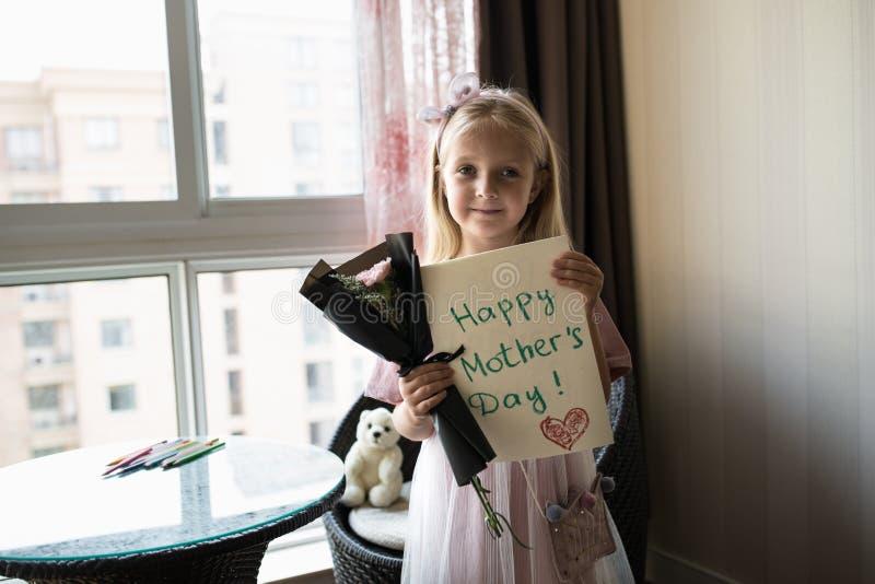 Liten dotter som rymmer den målade vykortet och buketten av blommor för mamma Lyckligt mors dagbegrepp royaltyfri bild