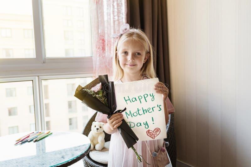 Liten dotter som rymmer den m?lade vykortet och buketten av blommor f?r mamma Lyckligt mors dagbegrepp royaltyfria bilder