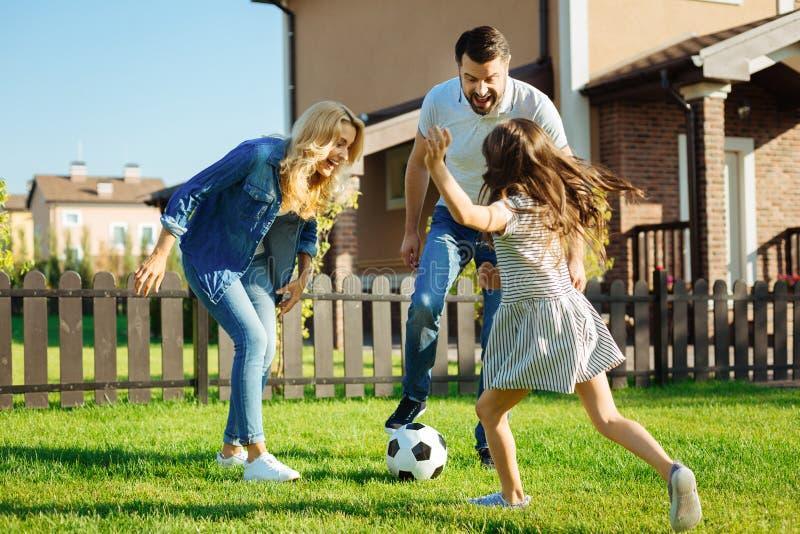 Liten dotter som spelar fotboll med henne föräldrar utanför royaltyfri foto