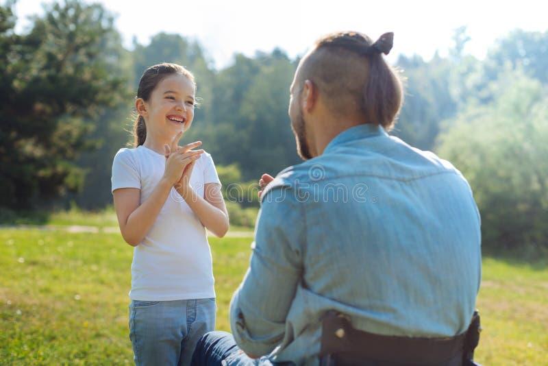 Liten dotter som spelar passande-en-kakan med henne rörelsehindrad fader royaltyfria bilder