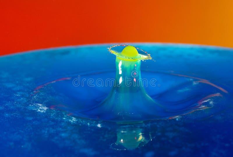 Liten droppefotografi: en gul droppe som faller in i det blåa vattnet arkivfoto