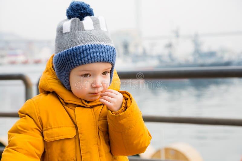 Liten eftertänksam pojke på stranden royaltyfria bilder