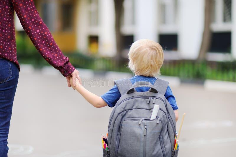 Liten elev med hans unga moder Första dag av grundskola för barn mellan 5 och 11 år royaltyfria bilder