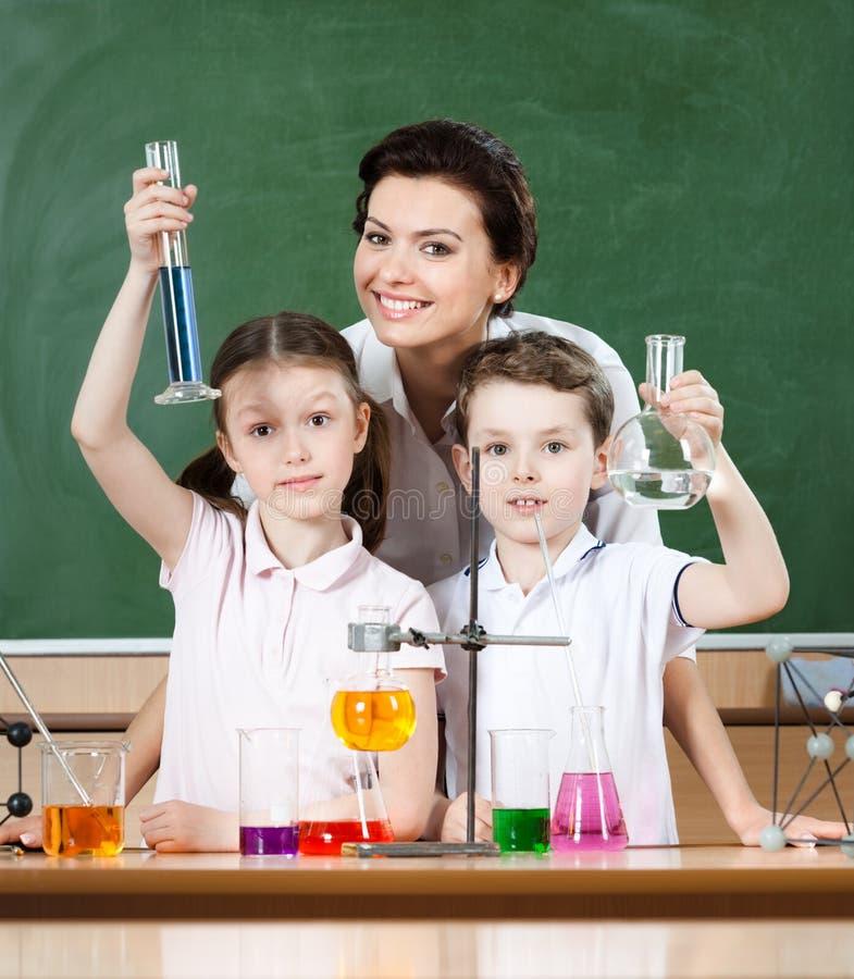 Liten elevstudykemi med deras lärare arkivfoton