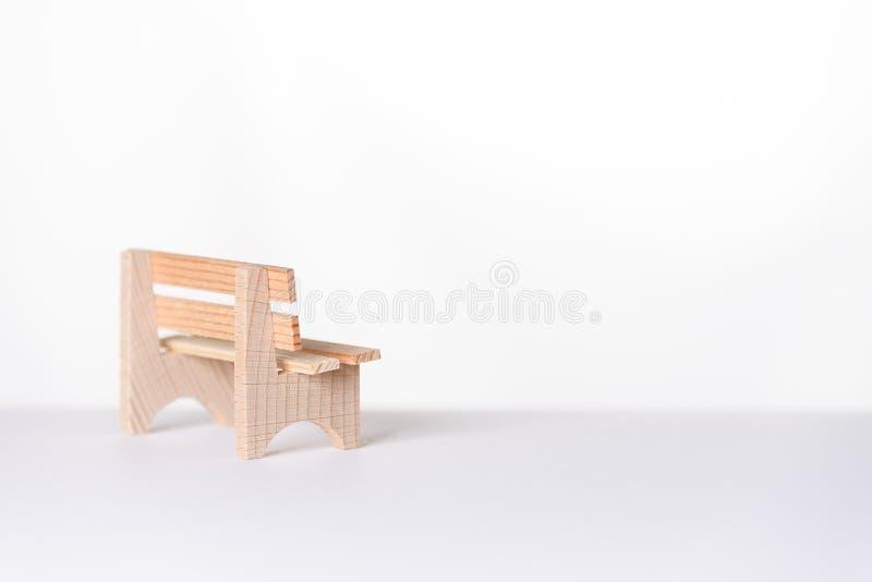 Liten enkel lantlig träbänk i ett vitt rum royaltyfri bild