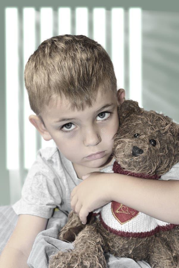 Liten ensam pojke med en nallebjörn arkivfoton