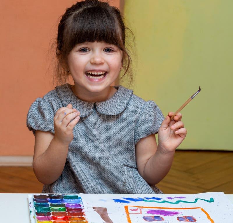 Liten europeisk flickamålning på tabellen inomhus fotografering för bildbyråer