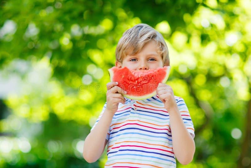 Liten förskole- ungepojke som äter vattenmelon i sommar royaltyfria bilder