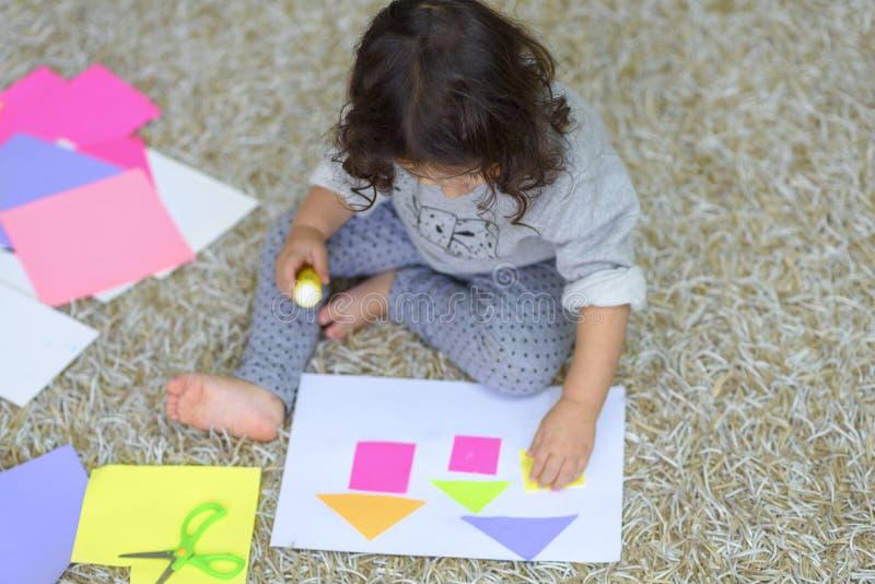Liten förskolebarnlitet barnflicka som limmar färgrikt papper arkivfoton