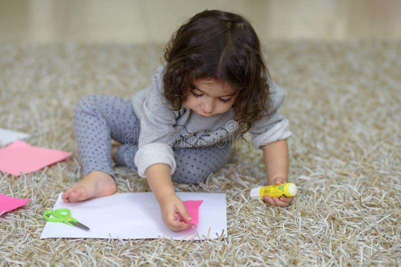Liten förskolebarnlitet barnflicka som limmar färgrikt papper arkivfoto