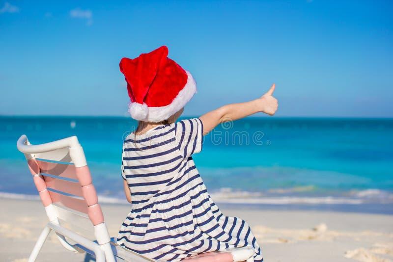 Liten förtjusande flicka i röda Santa Hat på stranden royaltyfri bild