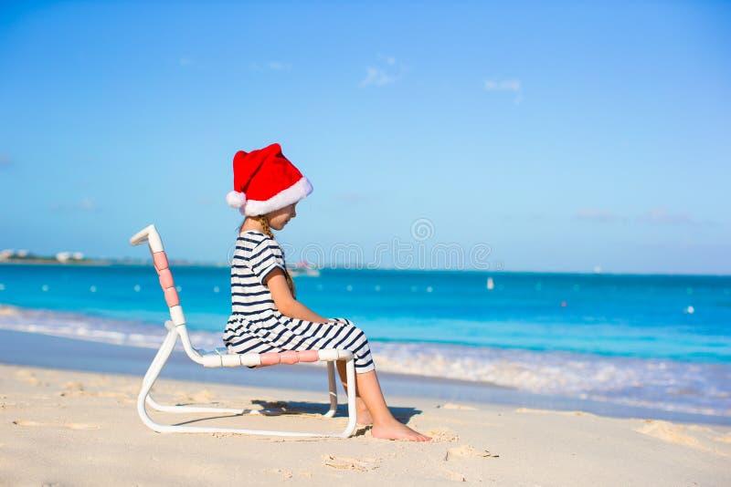 Liten förtjusande flicka i röda Santa Hat på stranden arkivfoton