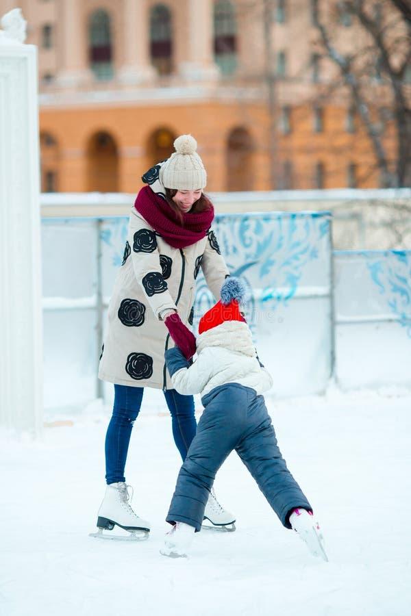 Liten förtjusande flicka med modern som åker skridskor på is-isbana med modern royaltyfria foton