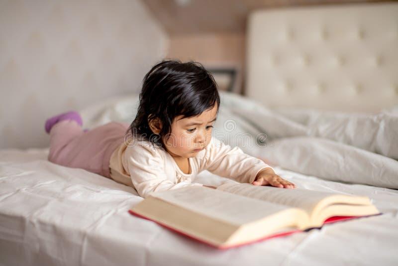 Liten förtjusande flicka som koncentreras på att läsa en bok, liten bokmal arkivfoton