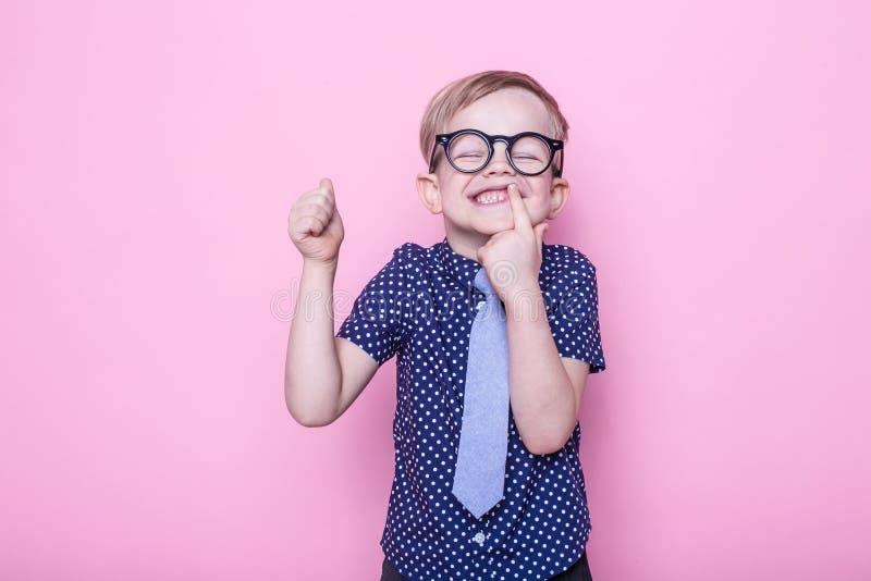 Liten förtjusande pojke i band och exponeringsglas skola förträning Mode Studiostående över rosa bakgrund arkivbilder