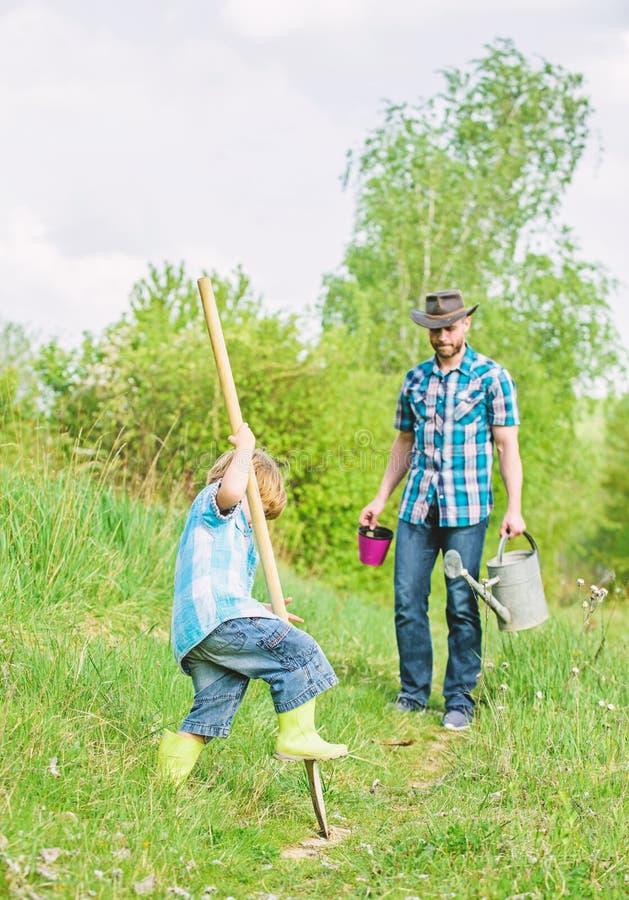 liten fader f?r pojkebarnhj?lp, i att bruka ny livstid jorder och g?dningsmedel fader och son som planterar stamtr?det Lyckligt royaltyfri foto