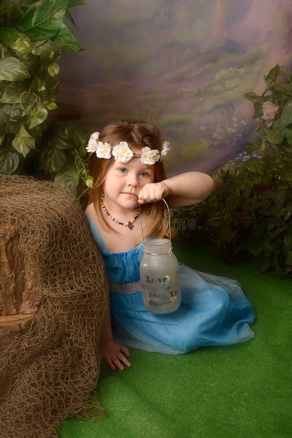 Liten fe i älvornas rike Liten flicka med feer i en krus royaltyfria bilder