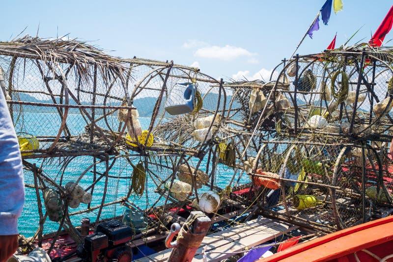 Liten fiskare Boat i havet som fångar en tioarmad bläckfisk med många hjälpmedel och fällor royaltyfria foton