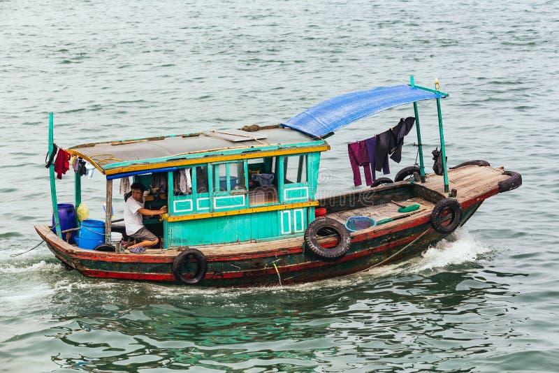 Liten fiskebåt över smaragdvatten med imponerande kalkstenöar i bakgrunden i sommar på Quang Ninh, Vietnam royaltyfri bild