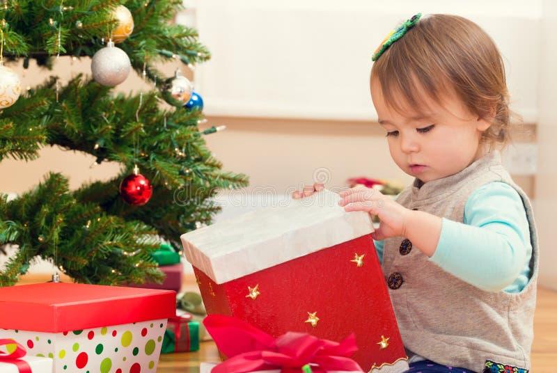 Liten flickaöppningsgåvor under hennes julgran royaltyfri foto